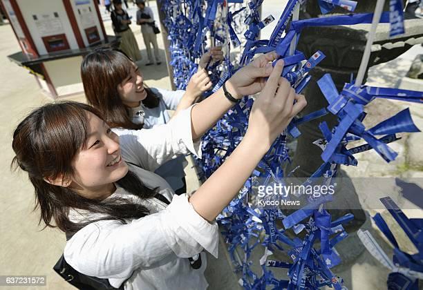 DAZAIFU Japan Women tie bluecolored 'omikuji' messages of fortune at the Dazaifu Tenmangu shrine in Dazaifu Fukuoka Prefecture on May 10 in support...