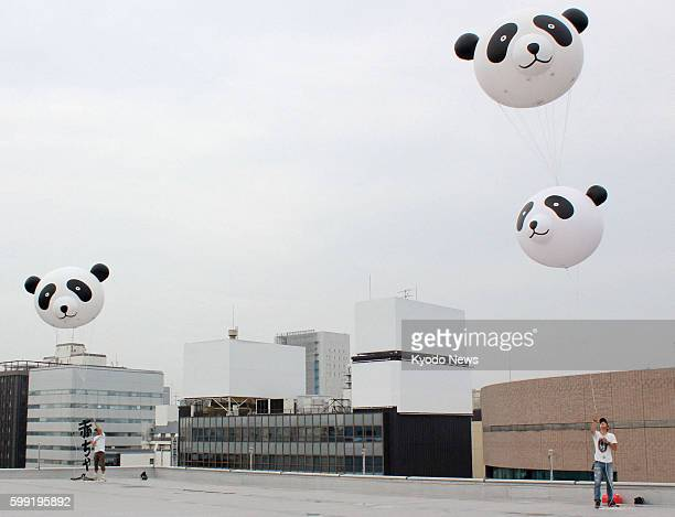 TOKYO Japan Workers set up pandashaped advertising balloons on the roof of the Matsuzakaya department store in Tokyo's Ueno district on July 6 2012...