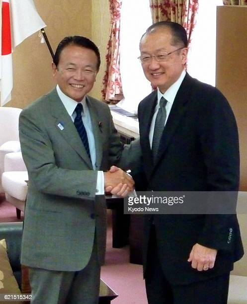 TOKYO Japan World Bank President Jim Yong Kim shakes hands with Japanese Finance Minister Taro Aso at the Finance Ministry in Tokyo on June 3 during...