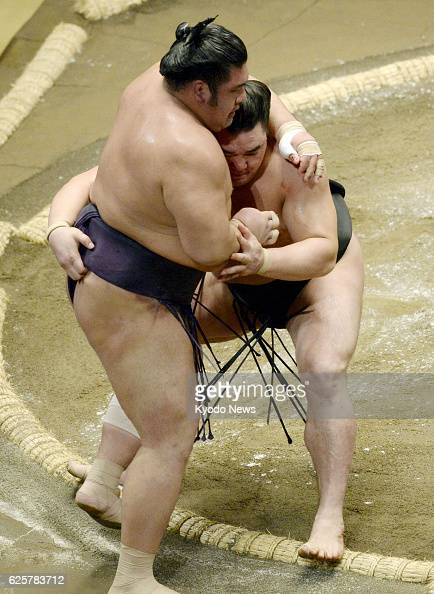 TOKYO Japan Yokozuna Harumafuji forces komusubi Tochiozan out of the ring on Sept 15 the opening day of the Autumn Grand Sumo Tournament at Ryogoku...