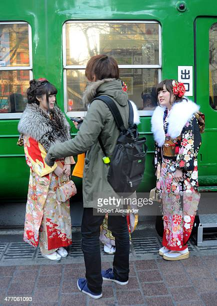 Japanaese teenage boy talks with two young Japanese women dressed in traditional kimonos in the Shibuya district of Tokyo Japan