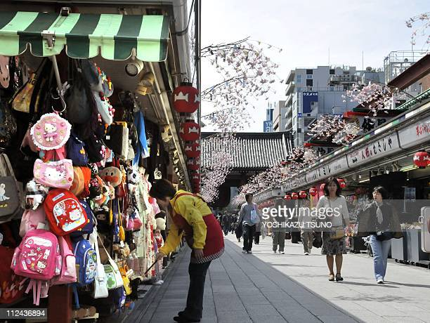 STORY 'Japandisasteraccidentnucleartourism' BY MADELEINE PRADELA sales clerk of a souvenir shop dusts her wares at Asakusa's main shopping mall in...