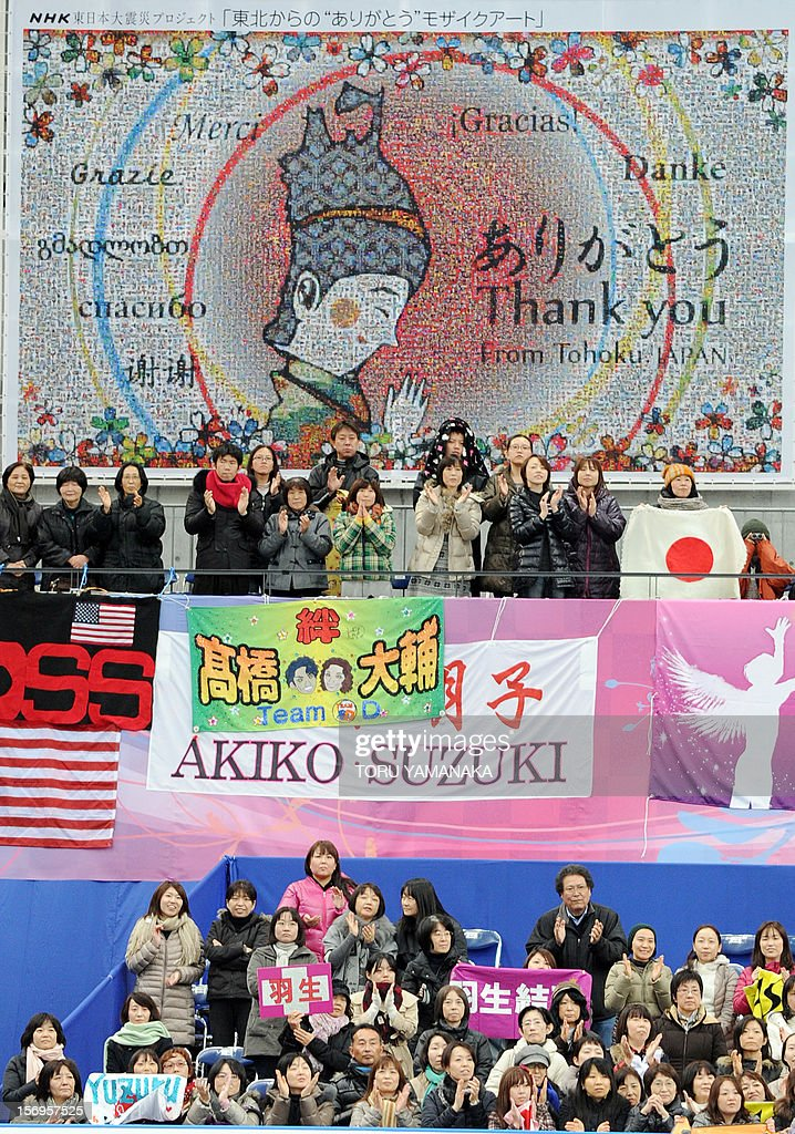 Japan-disaster-FSkate-Prix-JPN,FOCUS by Shigemi Sato In a picture taken on November 25, 2012, spectators applaud under a mosaic art piece expressing grattitude in different languages to countries for their support following the 2011 earthquake and tsunami disaster, during the NHK Trophy, the last leg of the six-stage ISU figure skating Grand Prix series at Sekisui Heim Super Arena in Rifu, northern Japan. The celebrations that rang out last weekend when a local schoolboy won the figureskating Grand Prix at an arena in Rifu were a far cry from its time as a morgue after Japan's tsunami. AFP PHOTO / Toru YAMANAKA