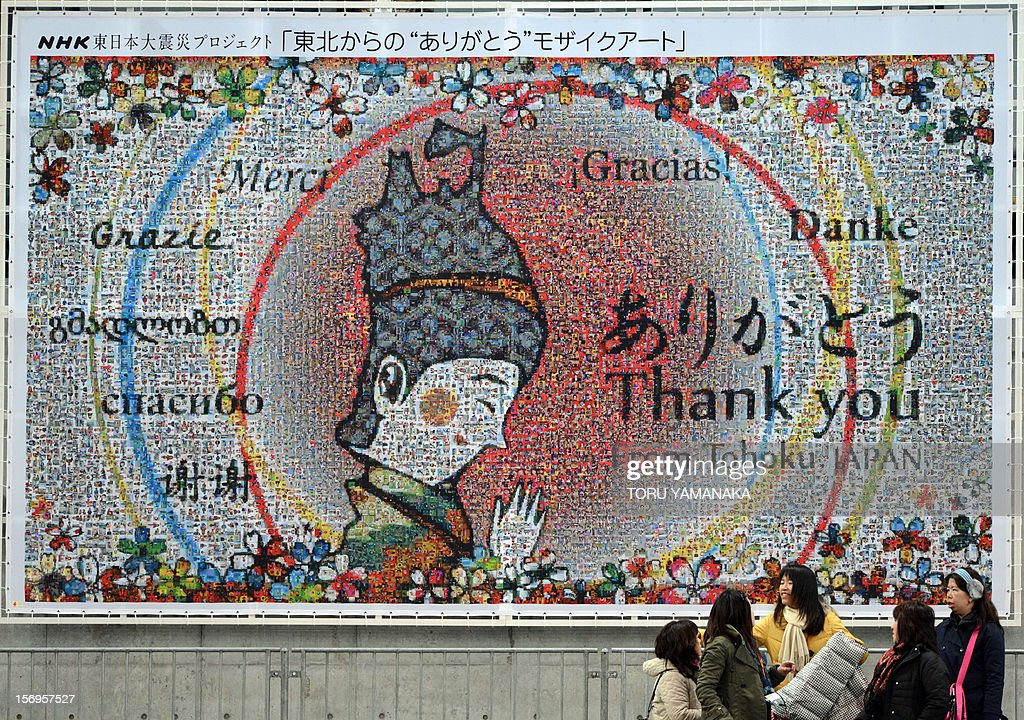 Japan-disaster-FSkate-Prix-JPN,FOCUS by Shigemi Sato In a picture taken on November 25, 2012, spectators chat under a mosaic art piece expressing grattitude in different languages to countries for their support following the 2011 earthquake and tsunami disaster, during the NHK Trophy, the last leg of the six-stage ISU figure skating Grand Prix series at Sekisui Heim Super Arena in Rifu, northern Japan. The celebrations that rang out last weekend when a local schoolboy won the figureskating Grand Prix at an arena in Rifu were a far cry from its time as a morgue after Japan's tsunami. AFP PHOTO / Toru YAMANAKA