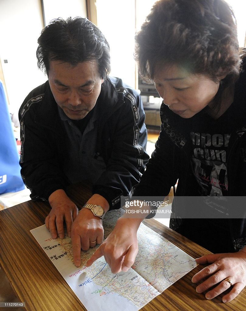 STORY 'Japan-disaster-nuclear-refugee,FOCUS' by Shingo ItoThis picture taken on March 28, 2011 shows Toshinori Sato, 57, (L) and his wife Tomoko, 55, pointing to their home on a map showing the various radii from the tsunami-hit Fukushima nuclear plant, at their makeshift shelter in Yokote city, Akita prefecture. Refugees who fled Japan's tsunami-hit nuclear reactors say they have been betrayed by the company that runs them, accusing embattled operator TEPCO of creating a 'man-made disaster'. Tens of thousands of people left their homes near the Fukushima Daiichi nuclear plant after it was crippled by the massive quake and tsunami that hit Japan on March 11, washing away whole towns. AFP PHOTO / TOSHIFUMI KITAMURA