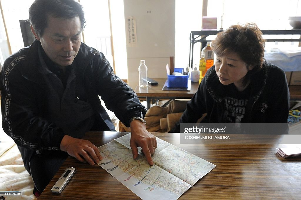 STORY 'Japan-disaster-nuclear-refugee,FOCUS' by Shingo ItoThis picture taken on March 28, 2011 shows Toshinori Sato, 57, (L) and his wife Tomoko, 55, pointing to their home on a map showing the various radii from the tsunami-hit Fukushima nuclear plant, at their makeshift shelter in Yokote city, Akita prefecture. Refugees who fled Japan's tsunami-hit nuclear reactors say they have been betrayed by the company that runs them, accusing embattled operator TEPCO of creating a 'man-made disaster'. Tens of thousands of people left their homes near the Fukushima Daiichi nuclear plant after it was crippled by the massive quake and tsunami that hit Japan on March 11, washing away whole towns.
