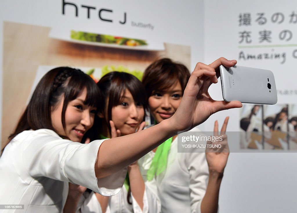 Japan-electronics-technology-camera,FOCUS by Hiroshi Hiyama This photo taken on November 20, 2012 shows models taking a self-portrait with a new 8 mega-pixel camera/smartphone called the 'HTCJ butterfly', produced by Taiwanese electronics maker HTC, in Tokyo. The soaring popularity of smartphones is crushing demand for point-and-shoot cameras, threatening the once-vibrant sector's survival as firms scramble to shift their strategy, analysts say. AFP PHOTO / Yoshikazu TSUNO