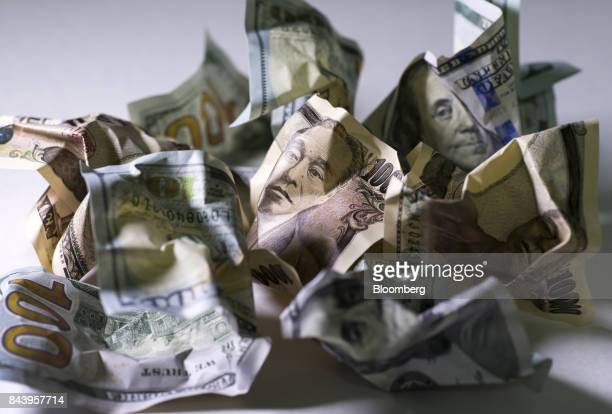 Japanese 10000 yen and US 100 dollar banknotes are arranged for a photograph in Tokyo Japan on Thursday Sept 7 2017 Japanese stocks fell as the yen...