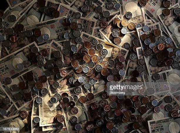 Japanese 10000 yen banknotes and coins of various denominations are arranged for a photograph in Tokyo Japan on Monday Feb 25 2013 The yen's...