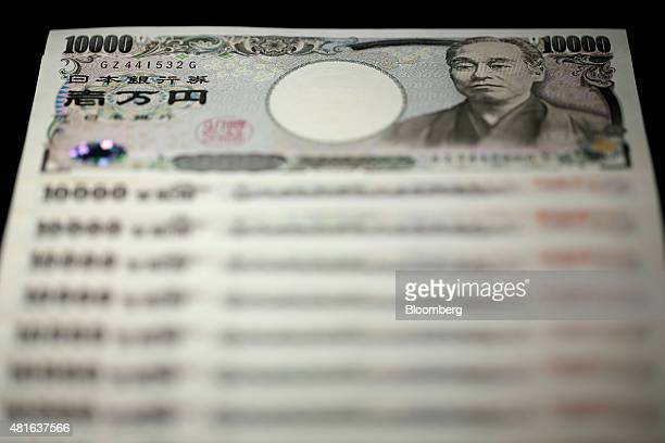 Japanese 10000 yen banknotes are arranged for a photograph in Tokyo Japan on Wednesday July 22 2015 The yen slipped 01 percent to 12403 per dollar...