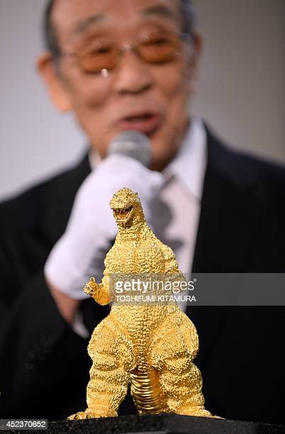 Japanese actor Haruo Nakajima speaks behind the 24cmtall and 15kilogram gold statue of Godzilla unveiled during a press preview of the Godzilla...