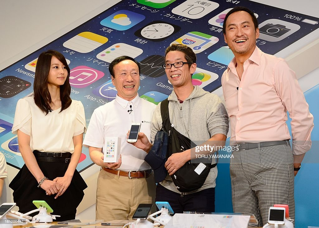 Japanese actor Ken Watanabe (R) and actress Maki Horikita (L) and President of Japan's biggest mobile carrier NTT Docomo Kaoru Kato (2nd L) pose with the first customer, Hidenori Sato (2nd R) of Apple's new iPhone 5s at a Docomo shop in Tokyo on September 20, 2013. Apple's new iPhone 5s and 'cheap' 5C models on September 20 went on sale in Japan. AFP PHOTO/Toru YAMANAKA