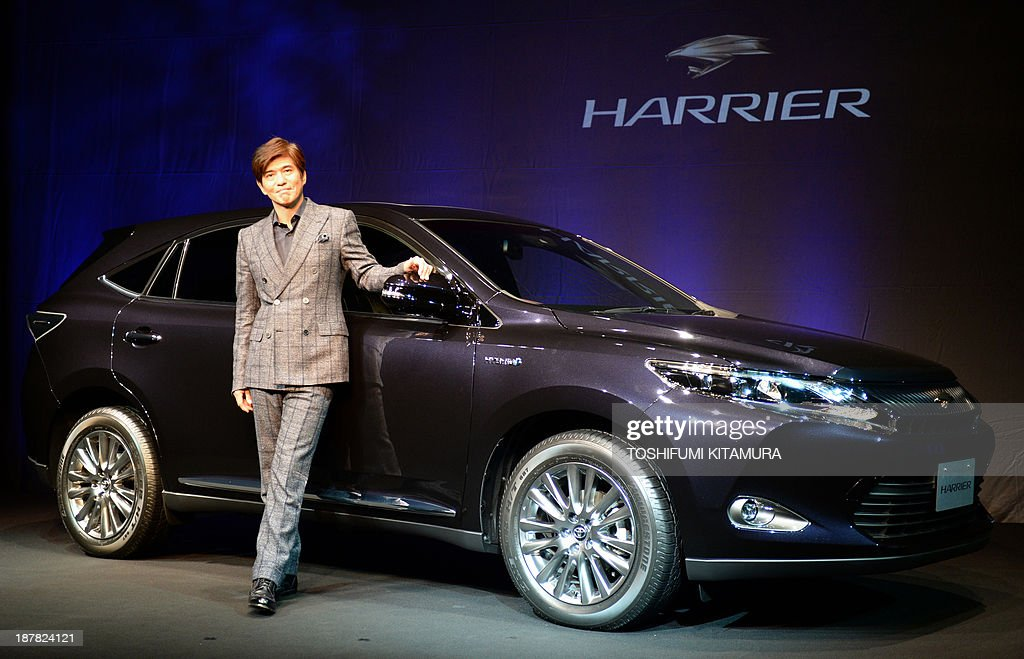 Japanese actor Koichi Sato stands beside Toyota's new SUV, Hybrid Harrier at a photo session during its press preview in Tokyo on November 13, 2013. Toyota will launch the redesigned 'Harrier,' the high-end crossover SUV in Japan on December 2 and its hybrid model will be released on January 15 next year.