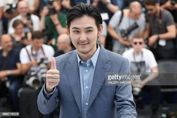 Japanese actor Ryuhei Matsuda gives the thumbsup as he poses on May 21 2017 during a photocall for the film 'Before We Vanish ' at the 70th edition...