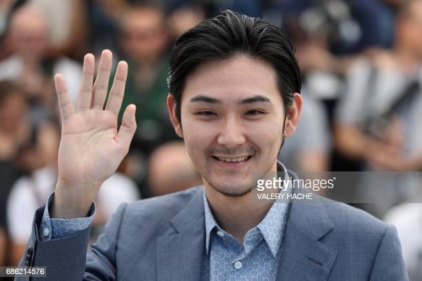 Japanese actor Ryuhei Matsuda waves on May 21 2017 during a photocall for the film 'Before We Vanish ' at the 70th edition of the Cannes Film...