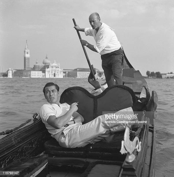 Japanese actor Toshiro Mifune lying on a gondola smoking a cigarette a gondolier rowing behind him and the Island of S George in the background...