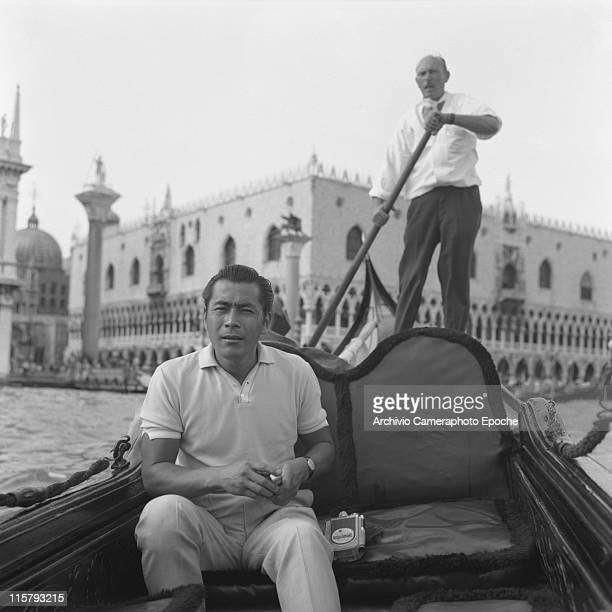 Japanese actor Toshiro Mifune sitting on a gondola with a cinecamera next to him a gondolier rowing behind him and St Mark Square in the background...