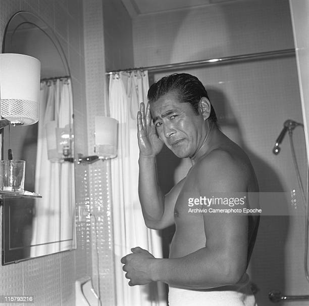 Japanese actor Toshiro Mifune standing barebreasted in front of the mirror in his bathroom wrapped in a towel oiling his hair Venice September 1961