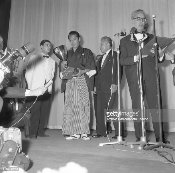 Japanese actor Toshiro Mifune wearing a haori kimono receiving the Volpi cup as best actor in the movie 'Yojimbo' people around him on the stage one...