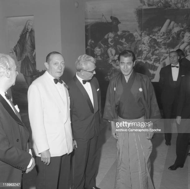 Japanese actor Toshiro Mifune wearing a haori kimono with a fan in his belt next to him the minister Folchi and the Biennale director Meccoli during...