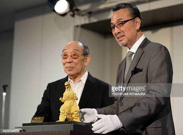 Japanese actors Akira Takarada and Haruo Nakajima pose beside the 24cmtall and 15kilogram gold statue of Godzilla unveiled during a press preview of...