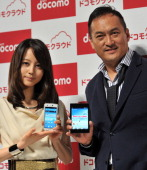 Japanese actors Ken Watanabe and Maki Horikita display new smartphones from Japan's mobile communication giant NTT DoCoMo at an unveiling ceremony in...