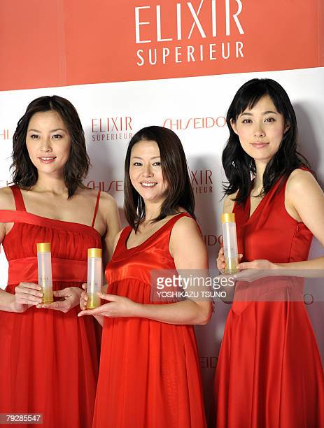 Japanese actress Asaka Seto Kyoko Koizumi and Kazue Fukiishi display skin care lotion bottles of Japanese cosmetics giant Shiseido as the company...