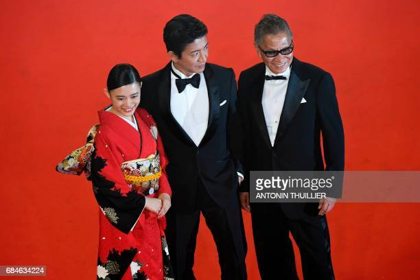 Japanese actress Hanna Sugisaki Japanese actor Takuya Kimura and Japanese director Takashi Miike pose on May 18 2017 as they arrive for the screening...
