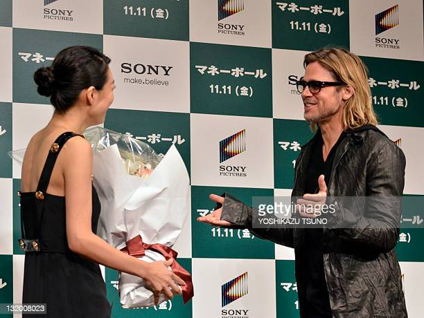 Japanese actress Kazue Fukiishi gives a bouqet of flowers to US actor Brad Pitt at a press conference for his latest movie 'Moneyball' in Tokyo on...