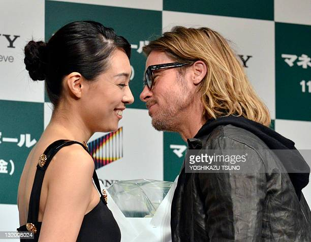 Japanese actress Kazue Fukiishi gives a bouqet of flowers to US actor Brad Pitt a press conference for his latest movie 'Moneyball' in Tokyo on...