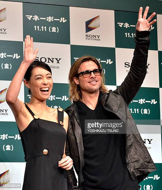 Japanese actress Kazue Fukiishi waves with US actor Brad Pitt as they attend a press conference for his latest movie 'Moneyball' in Tokyo on November...