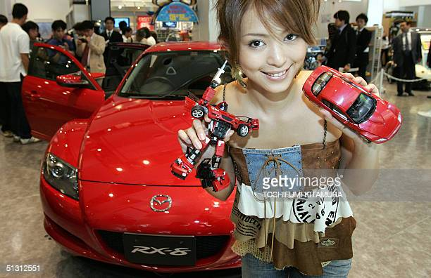 Japanese actress Mayuko Iwasa shows off Japanese toy maker Takara's latest robot toy 'Transformer BinalTec BT08 Mazda RX8' in front of Mazda RX8 car...