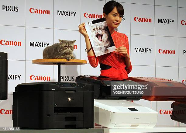 Japanese actress Mirei Kiritani poses with a photo during a promotion for Canon's new inkjet printers for personal and business use the 'Pixus' and...
