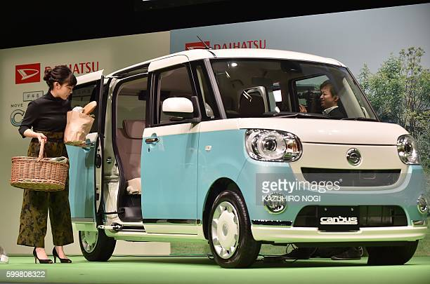 Japanese actress Mitsuki Takahata poses next to Daihatsu Motor's new mini passenger vehicle 'MOVE canbus' during a press preview to announce the...
