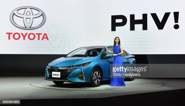 Japanese actress Satomi Ishihara poses beside a redesigned Toyota Motor Prius PHV during a press conference in Tokyo on February 15 2017 Toyota...
