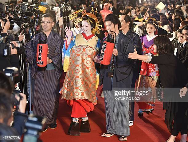 Japanese actress Yumi Adachi clad in traditional kimono costume and actors who performed in the movie 'A Courtesan with Flowered Skin' walk on the...