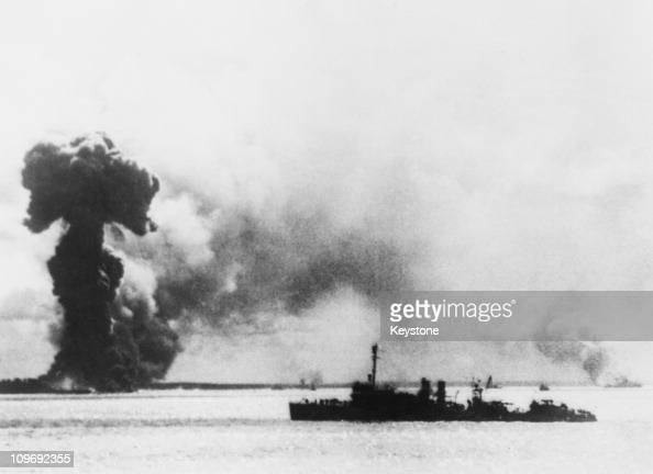A Japanese air attack on Port Darwin Australia during World War II 1942 In the foreground right is a US destroyer and behind it are the burning...