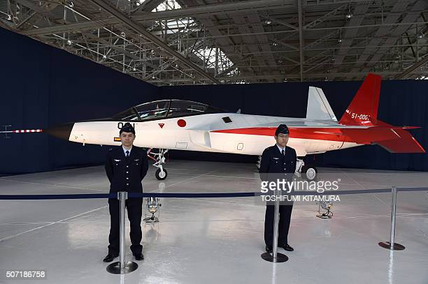 Japanese Air Self Defence Forces officers stand beside the X2 advanced technological demonstrator airplane at the Mitsubishi Heavy Industries factory...