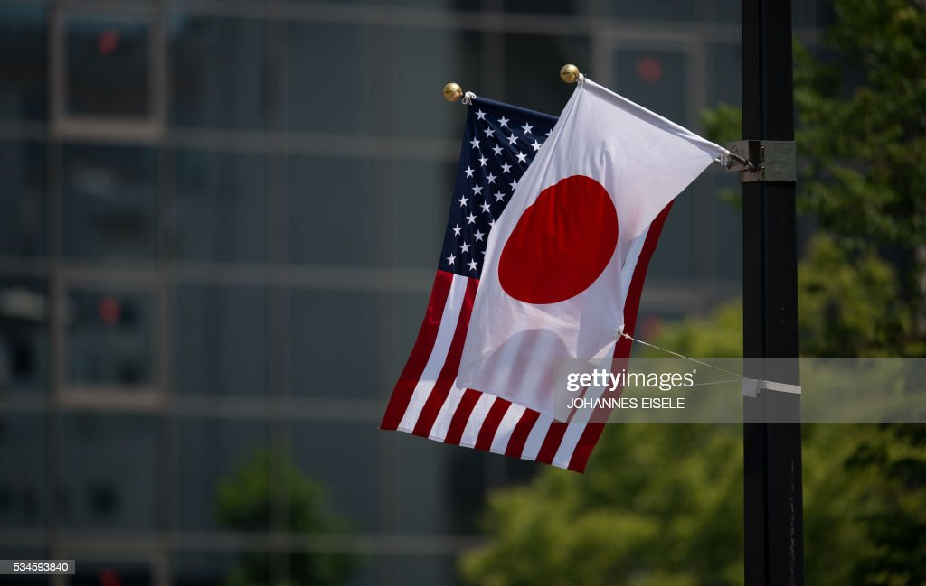 A Japanese and a US flag are seen next to the Hiroshima Peace Memorial in Hiroshima on May 27, 2017. US President Barack Obama was to make history later on May 27 when he travels to Hiroshima -- becoming the first sitting US leader to visit the site that ushered in the age of nuclear conflict. / AFP / JOHANNES