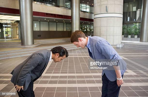 japanese and european businessmen salute at kyoto japan