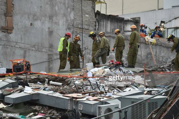 Japanese and Israeli rescuers take part in the search for survivors at a flattened building in Mexico City on September 22 2017 three days after a...