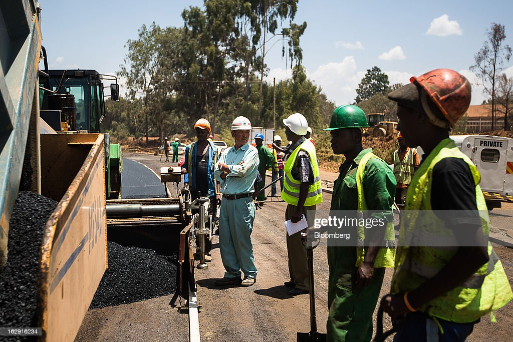 Japanese and Kenyan workers lay asphalt on a new road in Nairobi, Kenya, on Friday, March 1, 2013. Next week's presidential vote will be the first since disputed elections in 2007 triggered ethnic fighting in which more than 1,100 people died and another 350,000 fled their homes. Photographer: Trevor Snapp/Bloomberg via Getty Images