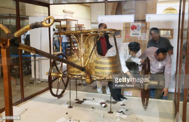 Japanese and local Egyptologists examine a chariot of King Tutankhamun at a museum in Cairo on March 28 before transferring the king's burial goods...
