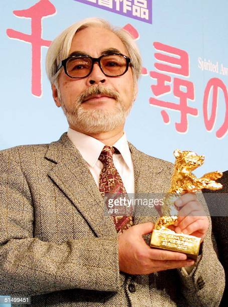 Japanese animated film director Hayao Miyazaki shows off the Golden Bear trophy the top prize of the Berlin Film Festival during a press conference...