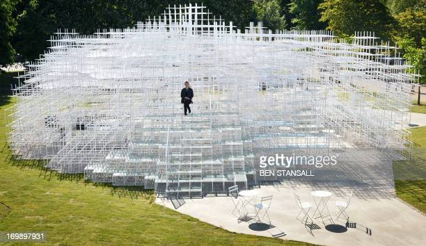 Japanese architect Sou Fujimoto poses for photographers with his Serpentine Gallery Pavilion structure at the Serpentine Gallery in London on June 4...