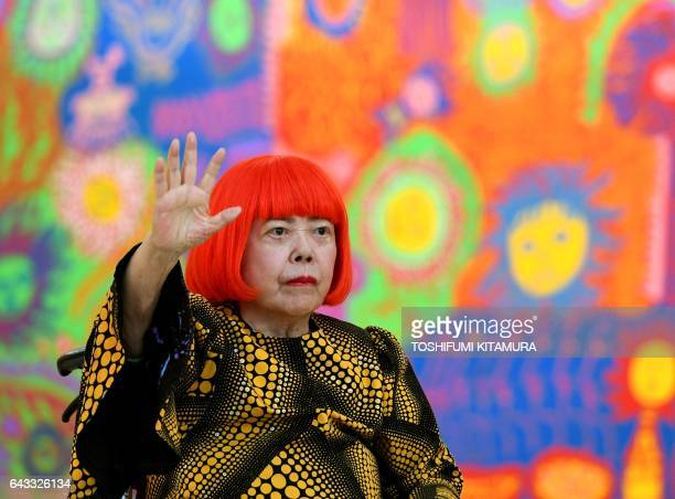 Japanese artist Yayoi Kusama waves at a photo session during a press preview of her exhibition titled 'My Eternal Soul' at the National Art Center in...