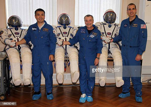 Japanese astronaut Koichi Wakata Russian cosmonaut Mikhail Tyurin and US astronaut Rick Mastracchio stand near their spacesuits during the preflight...