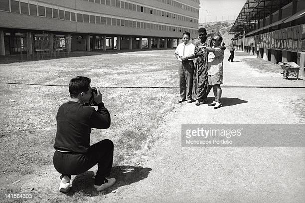 Japanese athlete photographing a group of people posing in the Olympic village during Rome Olympics Rome 1960