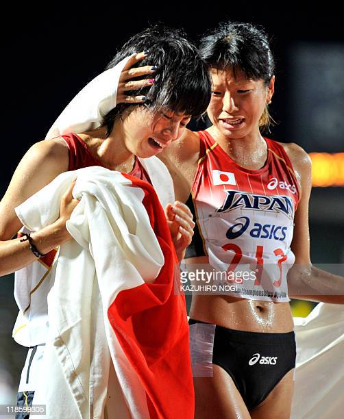 Japanese athletes Hitomi Niiya and Yuriko Kobayashi cry as they celebrate after finishing the women's 5000m final at the Asian Athletics...