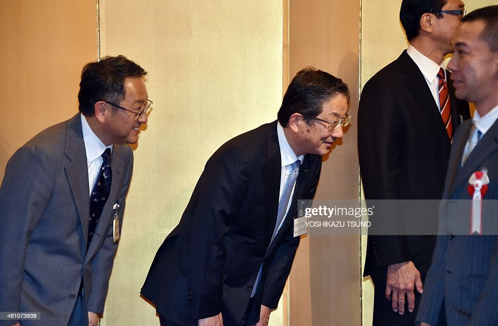 Japanese auto giant Toyota Motor president Akio Toyoda and Nissan Motor vice chairman Toshiyuki Shiga greet guests at a new year party hosted by the...